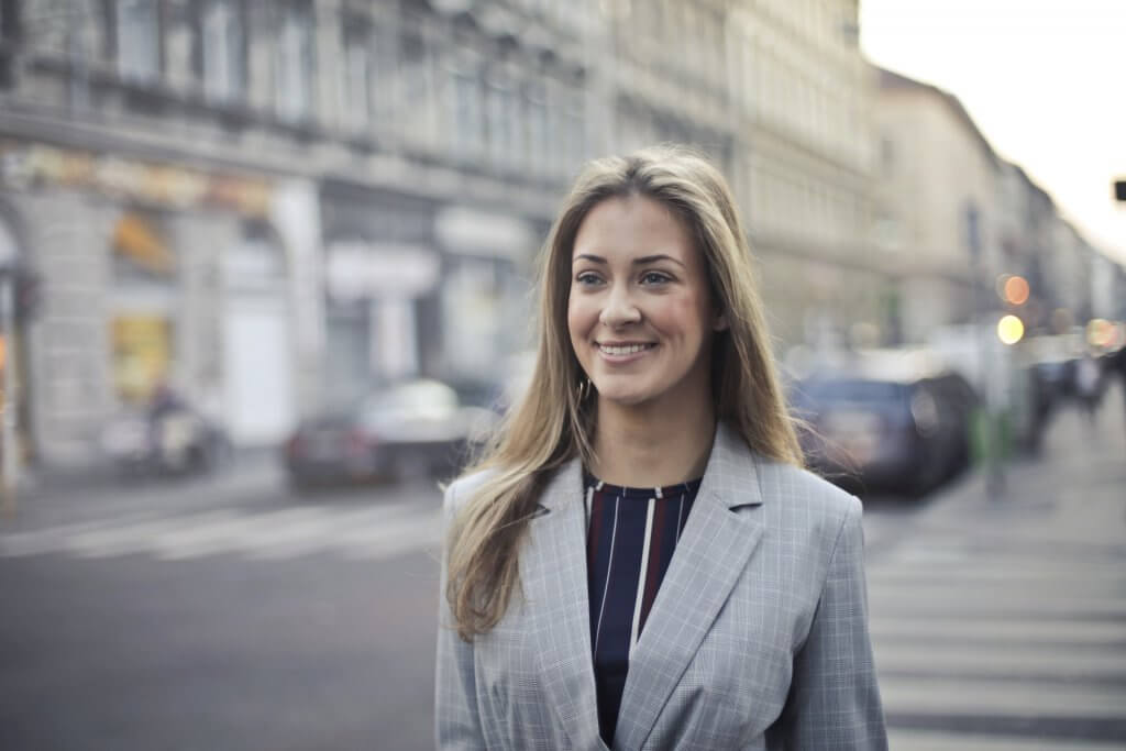 Business Woman Smiling on City Sidewalk