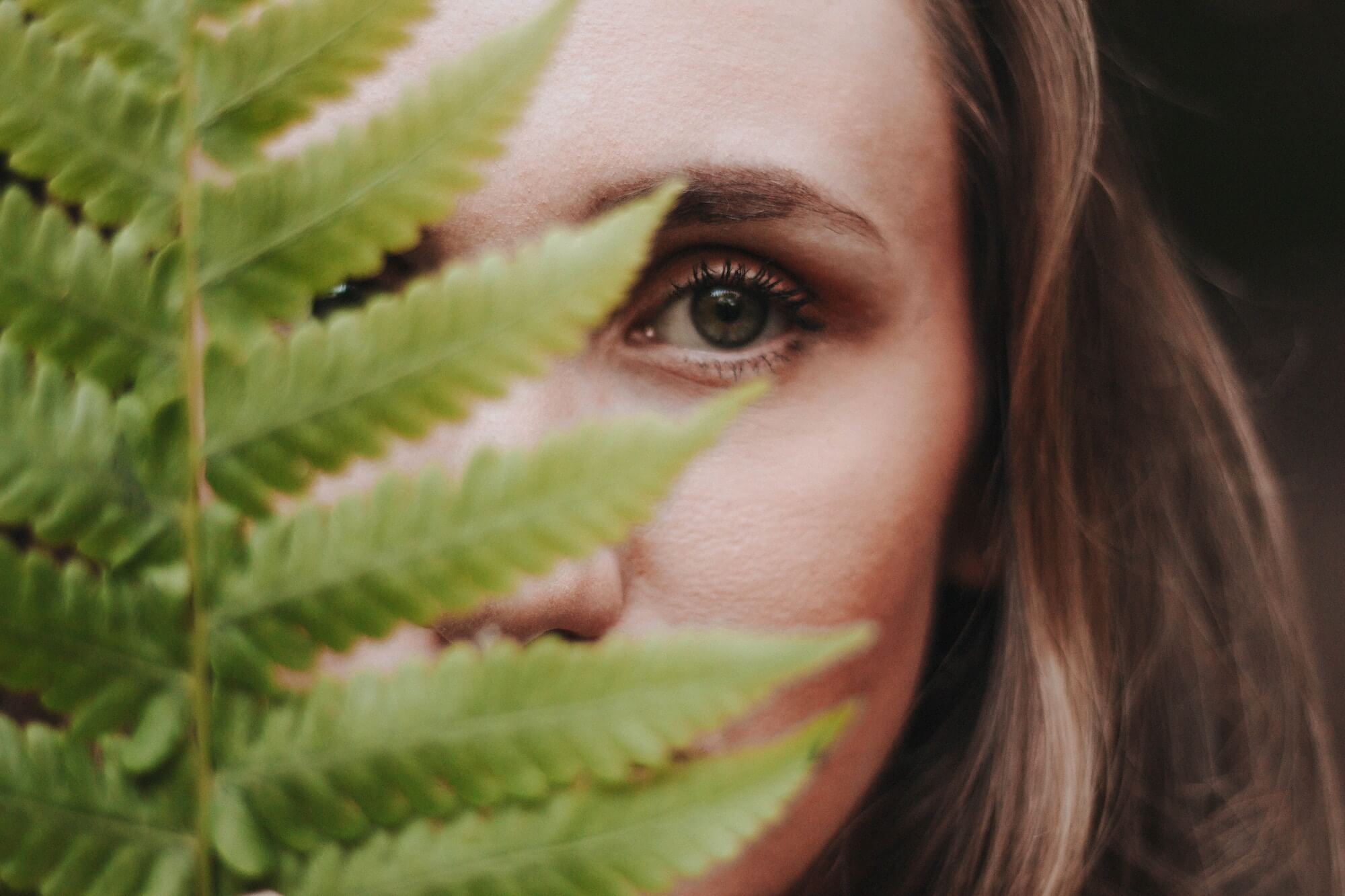 Woman Face Obscured by Fern