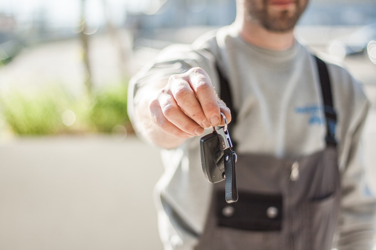 Man holding car keys to give to you