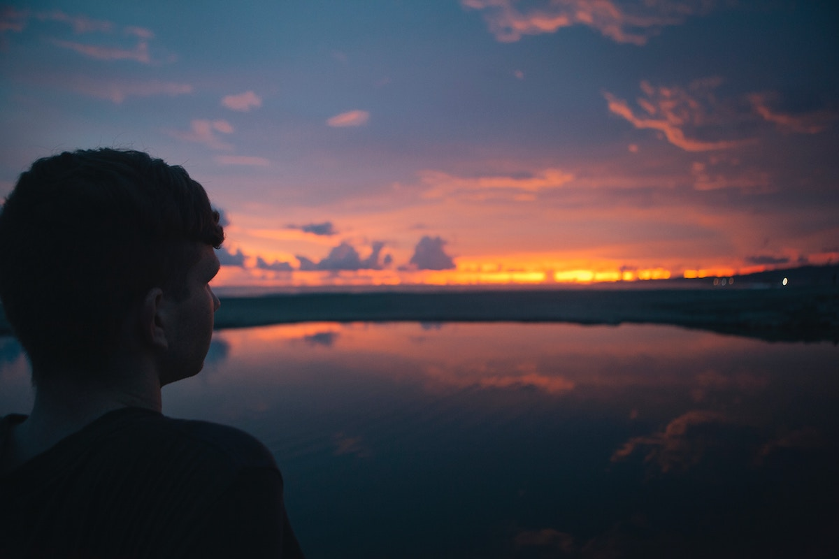 Silhouette of Man Looking at Sunset Over Lake