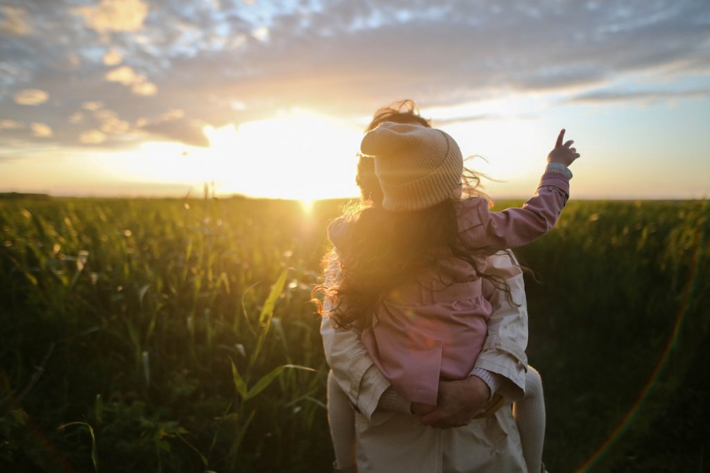 Woman holding and hugging child with field and sun in background