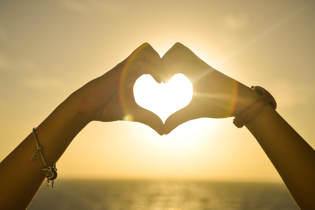 Hand gesture of heart shape with sun behind